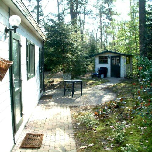zijkant bungalow met tuinhuis